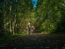 Οι ασιατικές ταξιδιωτικές διακοπές χαλαρώνουν με το ποδήλατο στο πάρκο φύσης Στοκ φωτογραφία με δικαίωμα ελεύθερης χρήσης