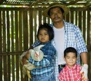 Οι ασιατικοί αγρότες διδάσκουν τα παιδιά τους για να φροντίσουν για τις εγκαταστάσεις με την υπομονή και την προσπάθεια Στοκ Φωτογραφίες