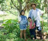 Οι ασιατικοί αγρότες διδάσκουν τα παιδιά τους για να φροντίσουν για τις εγκαταστάσεις με την υπομονή και την προσπάθεια Στοκ εικόνες με δικαίωμα ελεύθερης χρήσης