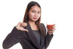 Οι ασιατικοί αντίχειρες γυναικών μισούν κάτω το χυμό ντοματών Στοκ Εικόνες
