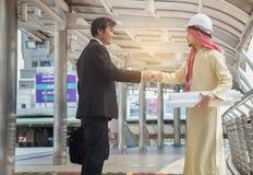 Οι ασιατικοί επιχειρηματίες και οι αραβικοί αρχιτέκτονες συμφωνούν τη χειραψία σχετικά με το α στοκ εικόνα με δικαίωμα ελεύθερης χρήσης