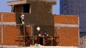 Οι ασιατικοί εργαζόμενοι γεμίζουν επάνω το κτήριο τούβλου με το τσιμέντο απόθεμα βίντεο