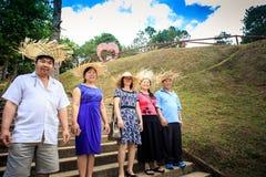 Οι ασιατικοί λαοί στα καπέλα αχύρου θέτουν στο πέτρινο κλιμακοστάσιο στο πάρκο Στοκ Φωτογραφίες