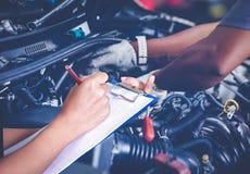 Οι ασιατικοί μηχανικοί και οι τεχνικοί γυναικών ελέγχουν το μηχανικό και στοκ εικόνα