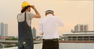 Οι ασιατικοί μηχανικοί που στέκονται στη στέγη για να δουν το βράδυ βλέπουν φιλμ μικρού μήκους