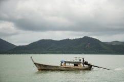 Οι ασιατικοί ταϊλανδικοί λαοί που οδηγούν την ξύλινη βάρκα μηχανών στη θάλασσα για στέλνουν Στοκ Φωτογραφίες
