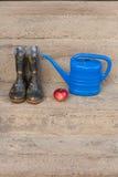 Οι λαστιχένιες μπότες, η κόκκινη Apple και το μικρό μπλε πότισμα μπορούν Στοκ Φωτογραφίες