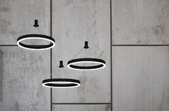 Οι ασυνήθιστες πηγές φωτός κρεμούν στο υπόβαθρο ενός μαρμάρινου τοίχου Λαμπτήρες υπό μορφή φωτεινού δαχτυλιδιού Στοκ φωτογραφίες με δικαίωμα ελεύθερης χρήσης