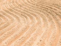 Οι αφηρημένες γραμμές καμπυλών γράφουν στην άμμο Στοκ εικόνα με δικαίωμα ελεύθερης χρήσης