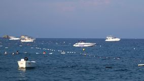 Οι βάρκες κυλούν στα κύματα κοντά στη θάλασσα, οι άνθρωποι λούζουν στη θάλασσα φιλμ μικρού μήκους