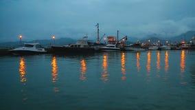 Οι βάρκες μηχανών που ελλιμενίστηκαν κοντά στην αποβάθρα φώτισαν τή νύχτα τα φω'τα που απεικονίζουν στο νερό φιλμ μικρού μήκους