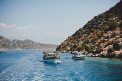 Οι βάρκες πλέουν το καλοκαίρι στη Μεσόγειο με το κυανό νερό μεταξύ των βουνών και των λόφων Στοκ Φωτογραφίες