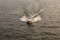 Οι βιασύνες βαρκών κατά μήκος του νερού, που αφήνει ένα ίχνος πίσω Στοκ εικόνα με δικαίωμα ελεύθερης χρήσης