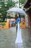 Οι βιετναμέζικες γυναίκες φορούν την ομπρέλα εκμετάλλευσης dai AO στη βροχή Στοκ εικόνες με δικαίωμα ελεύθερης χρήσης