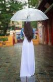 Οι βιετναμέζικες γυναίκες φορούν την ομπρέλα εκμετάλλευσης dai AO στη βροχή Στοκ Φωτογραφία