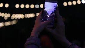 Οι βλαστοί κοριτσιών σε μια νύχτα smartphone ανάβουν τα Χριστούγεννα και το υπόβαθρο γιρλαντών απόθεμα βίντεο