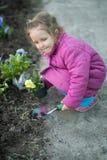 Οι βοήθειες κοριτσιών φυτεύουν τα λουλούδια στοκ εικόνες