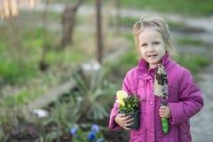 Οι βοήθειες κοριτσιών φυτεύουν τα λουλούδια στοκ εικόνα