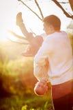 Οι βοήθειες μπαμπάδων υποστηρίζουν το αγόρι που κρεμά στον κλάδο ενός δέντρου, ήλιοι Στοκ Εικόνα