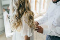 Οι βοήθειες νεόνυμφων στερεώνουν ένα γαμήλιο φόρεμα η νύφη πριν από την τελετή γάμος σκαλοπατιών πορτρέτου φορεμάτων έννοιας νυφώ Στοκ Εικόνες