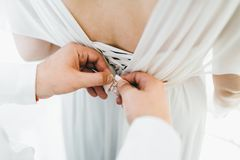 Οι βοήθειες νεόνυμφων στερεώνουν ένα γαμήλιο φόρεμα η νύφη πριν από την τελετή γάμος σκαλοπατιών πορτρέτου φορεμάτων έννοιας νυφώ Στοκ φωτογραφία με δικαίωμα ελεύθερης χρήσης