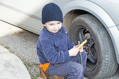 Οι βοήθειες παιδιών αποσυναρμολογούν μια ρόδα αυτοκινήτων Στοκ Φωτογραφίες