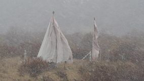 Οι βουδιστικές σημαίες προσευχής ταλαντεύθηκαν στον αέρα κατά τη διάρκεια χιονοπτώσεων το χειμώνα σε Gannan, Κίνα Το κύμα σημαιών φιλμ μικρού μήκους