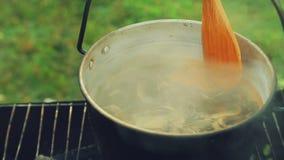 Οι βράζοντας πυρκαγιές σε μια πυρκαγιά στα μανιτάρια κατσαρολών ανακατώνουν ένα ξύλινο κουτάλι φιλμ μικρού μήκους
