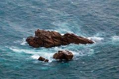Οι βράχοι προεξέχουν στο νερό, και τα κύματα κτυπούν σε τους Στοκ Εικόνες