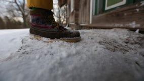 Οι γανωτές ατόμων γύρω από την πόρτα το χειμώνα, περπατούν και τινάζουν το χιόνι από τα παπούτσια του απόθεμα βίντεο