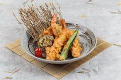 Οι γαρίδες και shiitake το tempura με τα τσίλι εξυπηρέτησαν στο μελάνι που χρωματίστηκε γύρω από το πιάτο πετρών στο χαλί γεύματο Στοκ Φωτογραφίες