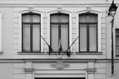 Οι γαλλικές σημαίες κρεμάστηκαν πέρα από τη μπροστινή πόρτα ενός σπιτιού στη Λίλλη (Γαλλία) Στοκ εικόνες με δικαίωμα ελεύθερης χρήσης