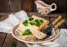 Οι γεμισμένες ρωσικές τηγανίτες κυλούν με το κρέας στο παραδοσιακό κύπελλο αργίλου στο ξύλινο υπόβαθρο εικόνα που τονίζεται Εκλεκ Στοκ Εικόνες