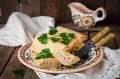 Οι γεμισμένες ρωσικές τηγανίτες κυλούν με το κρέας στο παραδοσιακό κύπελλο αργίλου στο ξύλινο υπόβαθρο εικόνα που τονίζεται Εκλεκ Στοκ Φωτογραφία