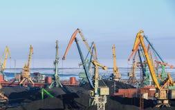 Οι γερανοί ατσάλινων σκελετών υπερφορτώνουν τον άνθρακα στο λιμένα στα σκάφη Στοκ Φωτογραφία