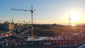 Οι γερανοί κατασκευής στηρίζονται ένα μεγάλο σπίτι στα περίχωρα 4K φιλμ μικρού μήκους