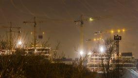 Οι γερανοί που λειτουργούν στη νύχτα και το χιόνι ανατινάζουν στην κατασκευή της κατοικήσιμης περιοχής στη ζώνηformerindustria απόθεμα βίντεο