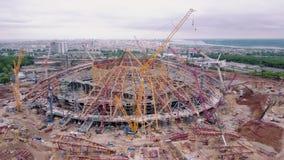 Οι γερανοί στέκονται γύρω από τη νέα σύγχρονη κατασκευή του σταδίου, εναέρια άποψη απόθεμα βίντεο