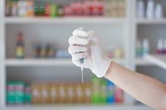 Οι γιατροί δίνουν με τη σύριγγα στην ιατρική και το φαρμακείο καταστημάτων στοκ φωτογραφία με δικαίωμα ελεύθερης χρήσης