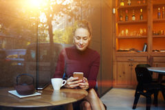 Οι γοητευτικές ευτυχείς θηλυκές ειδήσεις μόδας ανάγνωσης στο κύτταρο τηλεφωνούν κατά τη διάρκεια του προγεύματος στο εστιατόριο Στοκ φωτογραφία με δικαίωμα ελεύθερης χρήσης