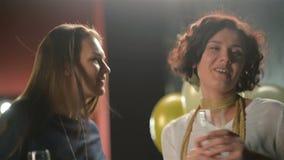 Οι γοητευτικές κυρίες χορεύουν και πίνουν το οινόπνευμα κατά τη διάρκεια ενός κόμματος Δύο γυαλιά εκμετάλλευσης γυναικών με CHAMP απόθεμα βίντεο
