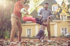 Οι γονείς έχουν τη διασκέδαση με τις κόρες γύρω από την περιστροφή στοκ φωτογραφίες