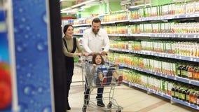 Οι γονείς κυλούν την κόρη τους στο κάρρο παντοπωλείων στην υπεραγορά φιλμ μικρού μήκους