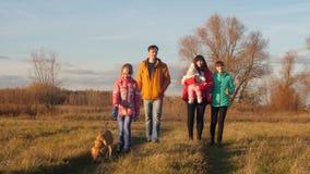 Οι γονείς με τα παιδιά και το μωρό περπατούν γύρω από το σκυλί εκμετάλλευσης στο λουρί απόθεμα βίντεο