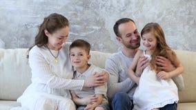 Οι γονείς με τα παιδιά στην κρεβατοκάμαρα στο κρεβάτι κάθονται και μιλούν φιλμ μικρού μήκους
