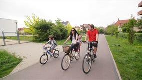 Οι γονείς με τα παιδιά τους οδηγούν στα ποδήλατα Ευτυχής χρόνος οικογενειακών εξόδων από κοινού απόθεμα βίντεο