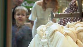 Οι γονείς με το γιο στέκονται σε ένα επίδειξη-παράθυρο του καταστήματος στην εμπορική λεωφόρο Το αγόρι παρουσιάζει σε ένα πράγμα  απόθεμα βίντεο
