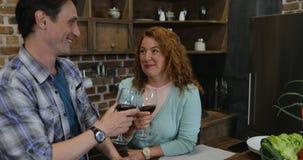 Οι γονείς πίνουν το κρασί εξετάζοντας τα παιδιά που περιμένουν μαζί το γεύμα μετά από να μαγειρεψουν στην κουζίνα στο σπίτι απόθεμα βίντεο