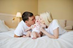Οι γονείς φιλούν το μωρό στο κρεβάτι Στοκ Φωτογραφία