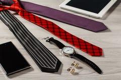 Οι γραβάτες μεταξιού χρώματος, ρολόι, μανικετόκουμπα, πωλούν το τηλέφωνο, ταμπλέτα σε μια GR Στοκ φωτογραφία με δικαίωμα ελεύθερης χρήσης